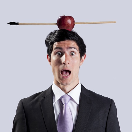 Scared businessman with a apple and arrow over his head photo