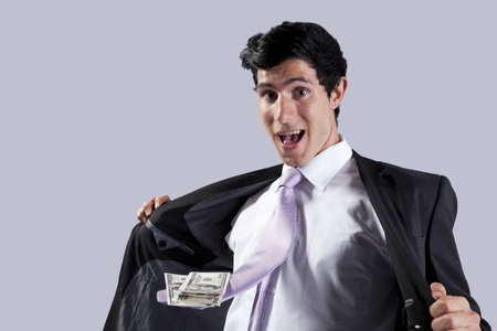 Businessman showing money in his flying necktie (isolated on gray) photo