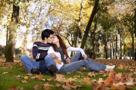 genegenheid: Liefde en affectie tussen een jong stel in het park in de herfst het seizoen (selectieve aandacht met ondiepe DOF)