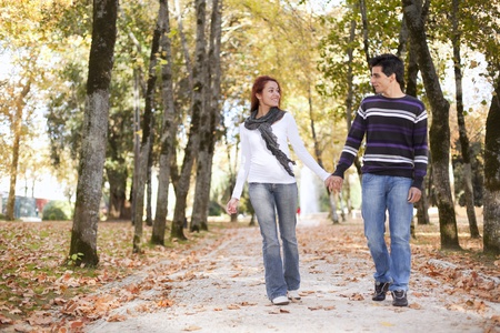 Love and affection between a young couple at the park in autumn season  photo