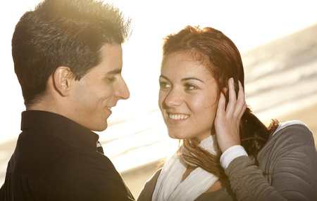 Love and affection between a young couple at the beach in sunny day (selective focus with shallow DOF) photo