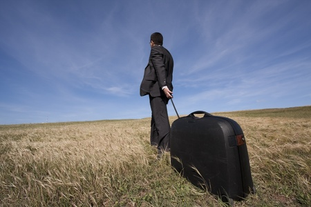 leaving: businessman with his luggage outdoor in the field