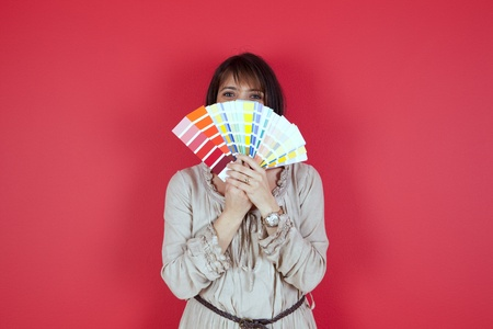 woman next to a red wall looking to a color paint palette (selective focus) Stock Photo - 10035729