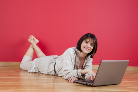 Woman using the laptop computer at her house floor, next to a red wall (selective focus) Stock Photo - 10035702