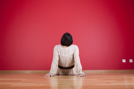Woman sitting on the floor looking up to a red wall Stock Photo - 10035721