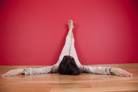 woman laying on the floor of her house next to a red wall photo