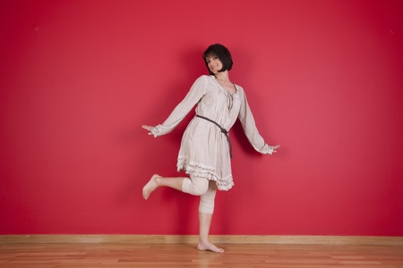 happy women dancing next to the red wall of his new house Stock Photo - 10035758