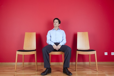 Businessman sited next to a red wall Stock Photo - 10035759