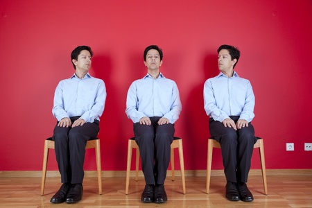 three nerd businessman with a suspicion look to each other, next to a red wall Stock Photo - 10035756