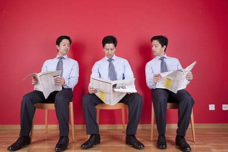 Three businessman peeking and reading the newspaper siting on a chair