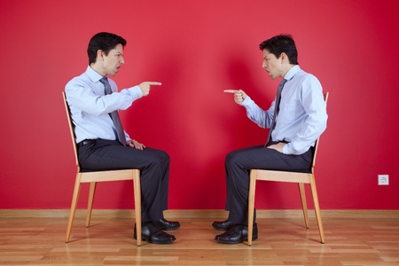 clone: Conflict between two twin businessman sited next to a red wall