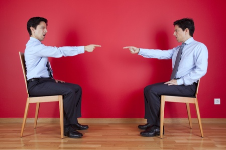 Conflict between two twin businessman sited next to a red wall photo