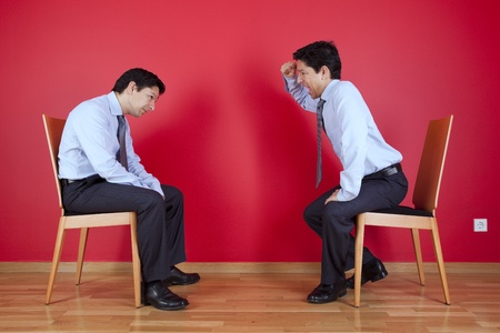Conflict between two twin businessman sited next to a red wall
