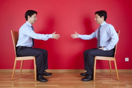 Handshake agreement between two twin businessman sitting in a chair next to a red wall Stock Photo