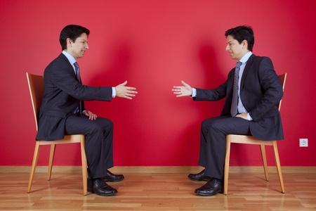 personas saludandose: Acuerdo apretón de manos entre dos empresario Gemelos sentado en una silla junto a un muro rojo Foto de archivo