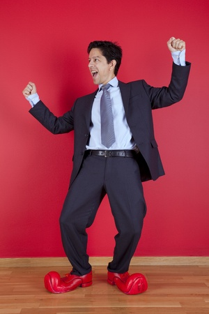Happy businessman next to a red wall with clown shoes Stock Photo - 10035750