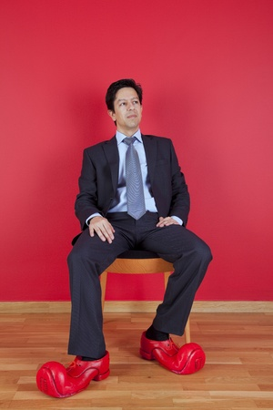 office shoes: Businessman sited next to a red wall with clown shoes