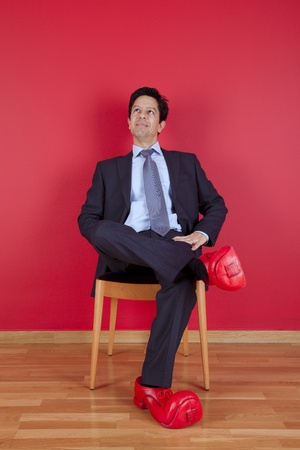 Businessman sited next to a red wall with clown shoes Stock Photo - 10035743