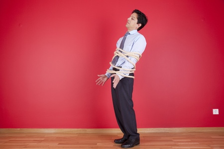 Businessman tied up with a rope struggle to get free Stock Photo - 10035738