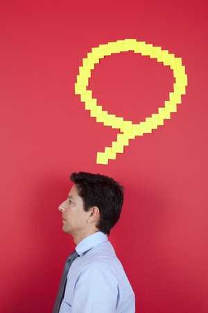 Businessman thinking next to a red wall  photo
