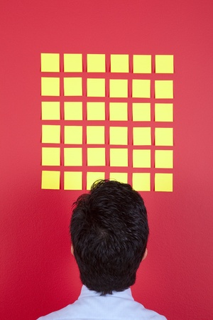 Businessman looking to yellow papers sticked at a red wall Stock Photo - 10035761