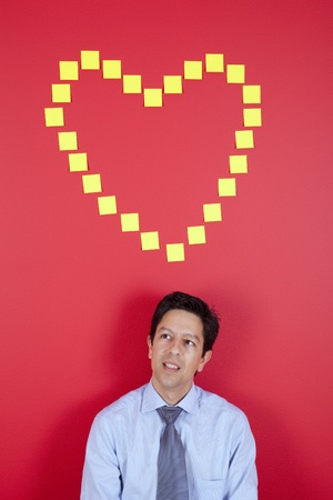 Businessman thinking about love next to a red wall photo