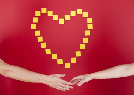 Hands touching next to a red wall with a heart symbol Stock Photo - 10035685