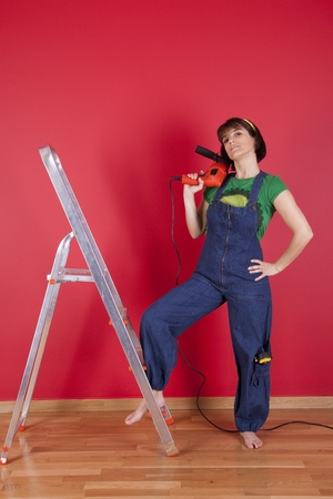 Woman at her house with a electric drill on her hand photo