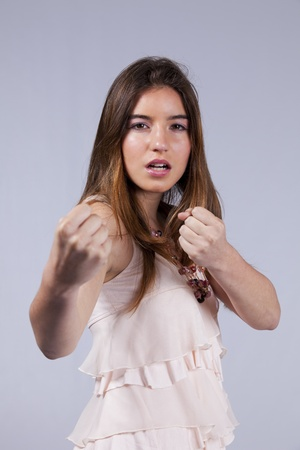 Teenage woman ready to fight with you (isolated on gray) photo
