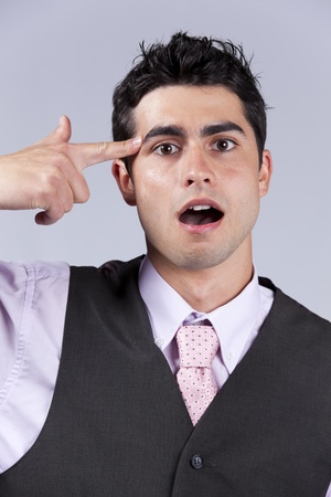 Young businessman despair pointing his finger to his head like shooting a gun  photo