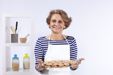 Beautiful and happy senior woman cooking at her kitchen Stock Photo - 10035669