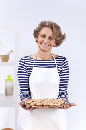 Beautiful and happy senior woman cooking at her kitchen Stock Photo - 10035824