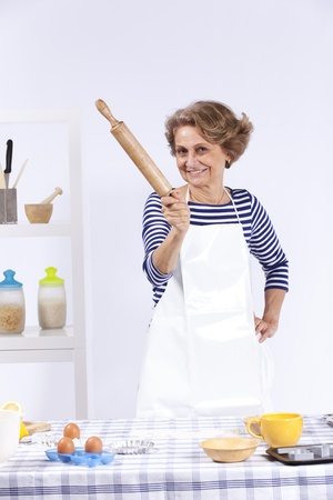 Senior woman at her kitchen showing you the rolling pin Stock Photo - 10035853