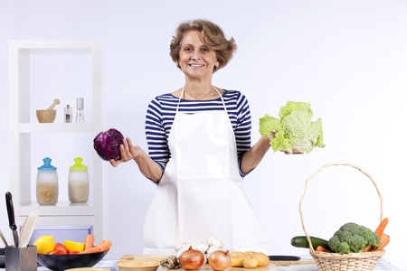 Beautiful and happy senior woman cooking at her kitchen Stock Photo - 10035852