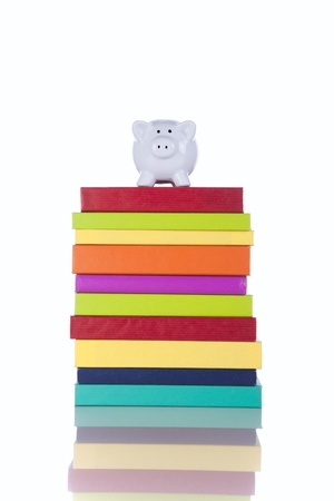 college fund savings: piggy bank over a stack of colorful books (isolated on white)
