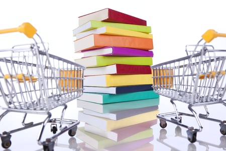 Stack of color books and a shopping cart (isolated on white) Stock Photo