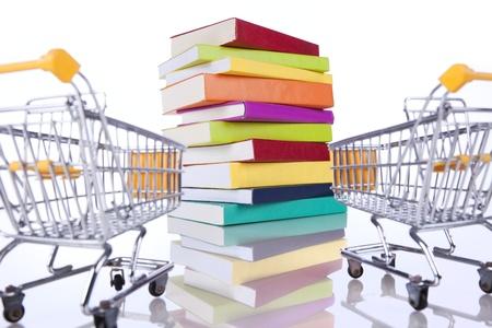 Stapel van kleur boeken en een winkelwagen (op wit wordt geïsoleerd) Stockfoto