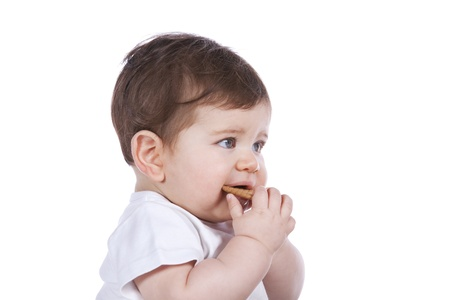 Handsome baby boy eating a small biscuit (isolated on white) photo