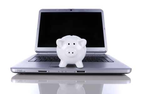 Piggybank over a modern laptop, the cost of technology and information (isolated on white) Stock Photo - 10035634