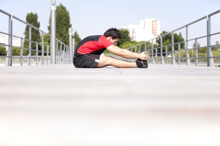 Athlete at the city park warming and stretching photo