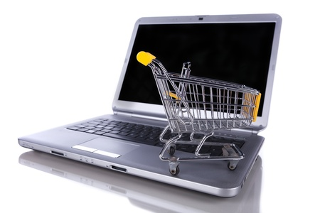 chrome cart: shopping-cart over a laptop isolated on white with reflection