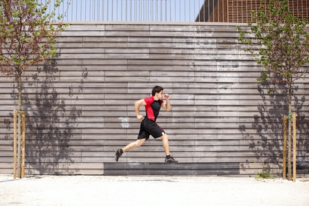 Men athlete running next to some city wall Stock Photo