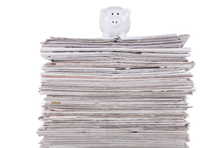Piggybank over a stack of newspaper (selective focus)