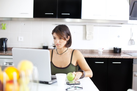 woman working with her laptop while eating her breakfast (selective focus with shallow DOF) Stock Photo - 10035659