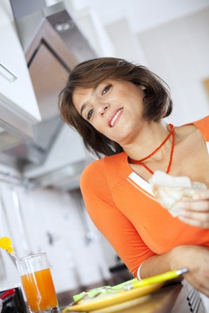 beautiful woman eating her breakfastl at her kitchen (selective focus with shallow DOF) photo