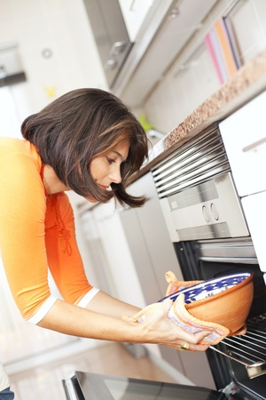 modern woman taken the food out of the kitchen oven