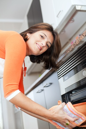 woman baking: happy modern woman open the kitchen oven