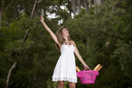 beautiful young woman in the woods with a basket full of bread Stock Photo - 11017654