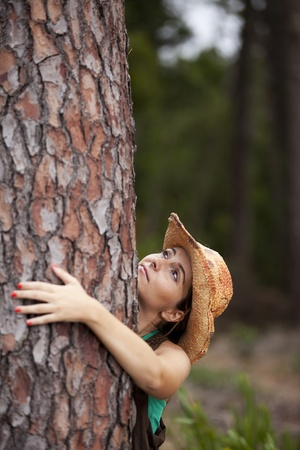 looking around: Young woman enjoying nature, embracing a tree trunk