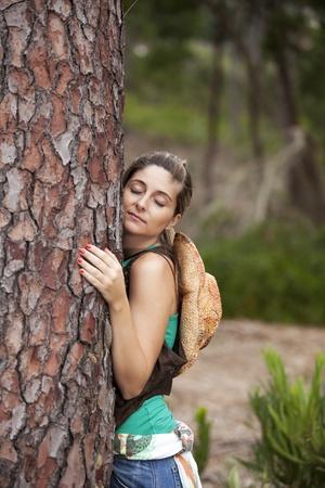 Young woman enjoying nature, embracing a tree trunk Stock Photo - 11017729